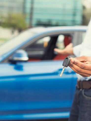 40416365 - male hand holding car keys offering new blue car on background